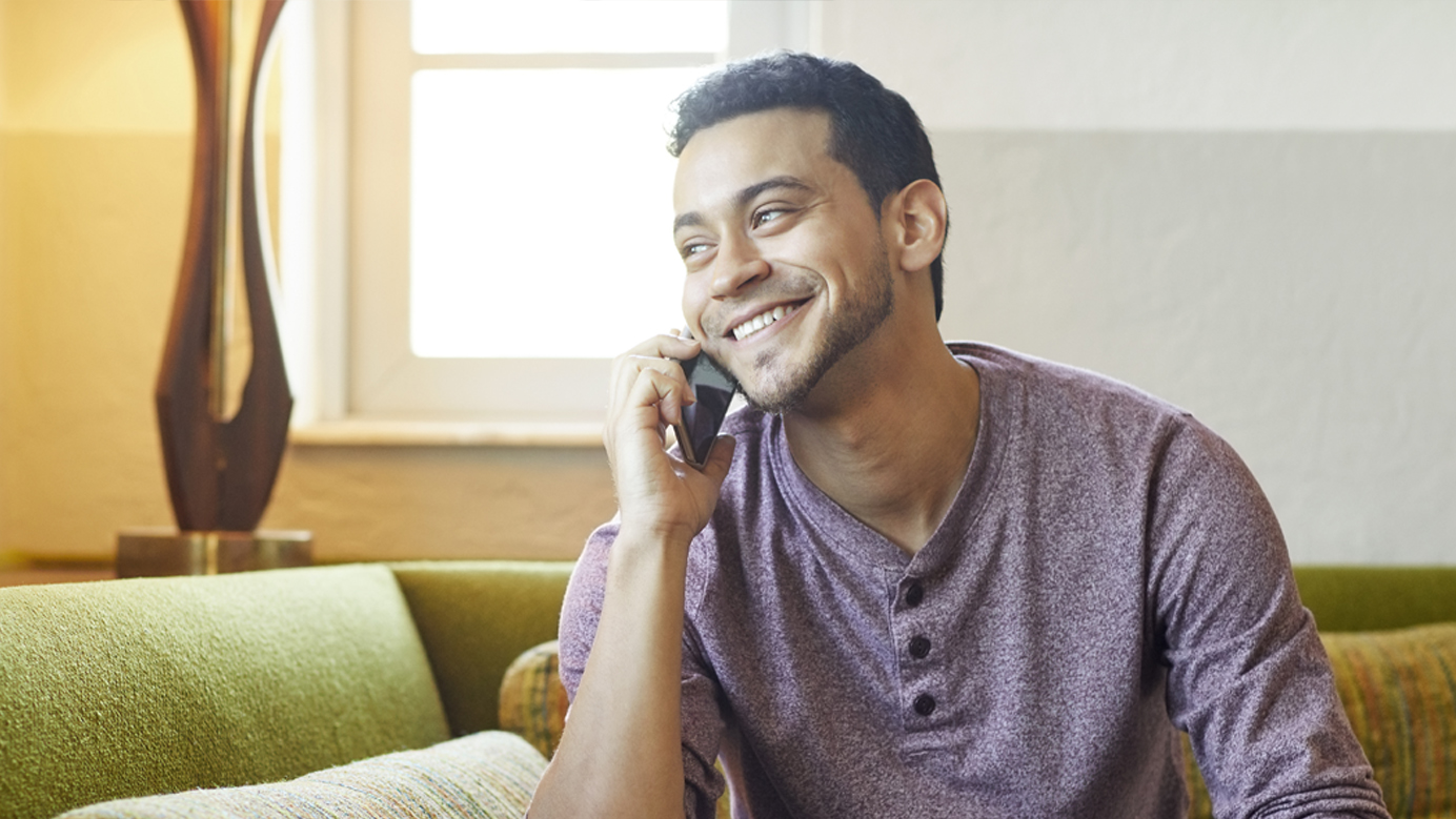 Smiling young man answering smart phone on couch
