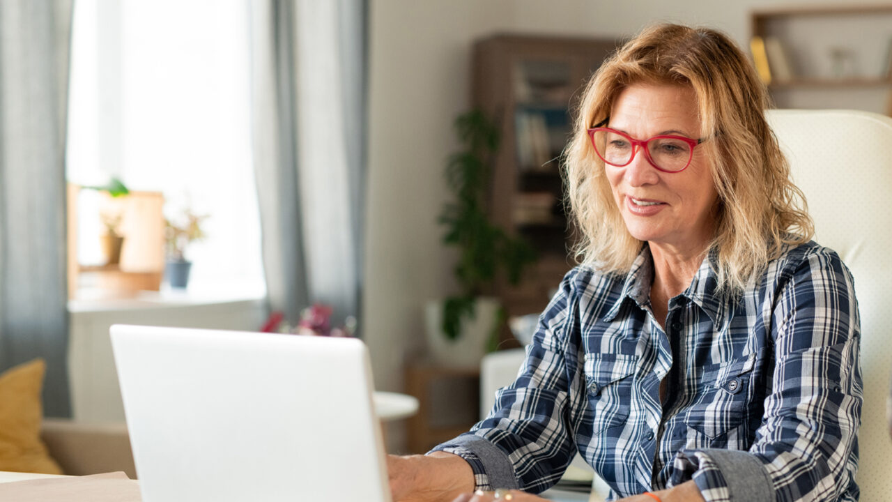 Smiling businesswoman in casual shirt and eyeglasses looking at laptop display